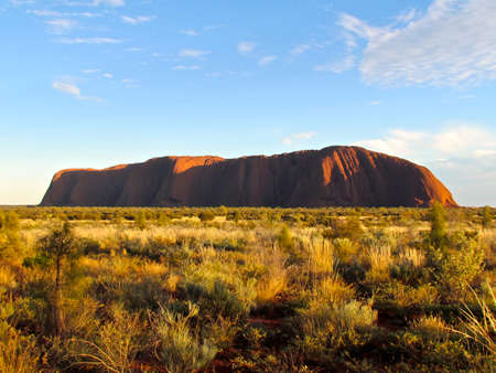 ayers: Ayers Rock, Uluru, at sunshine with clouds and bushes