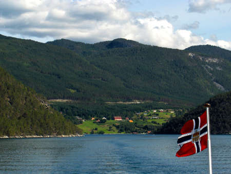scandinavian landscape: Norway fjords from a boat with flag