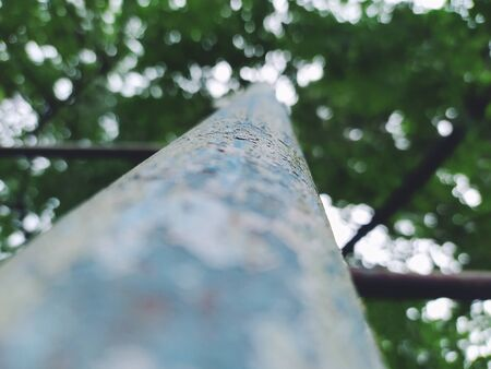 perspective view of an iron handrail against a background of leaves, dynamic range 스톡 콘텐츠