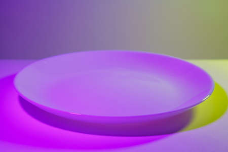 Abstract picture of simple ceramic white dish lit by two lights in ultraviolet contrasting colors. Pink and lime green. Centered close up.