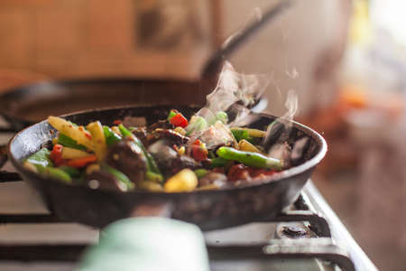 Red meat and colorful vegetables cooking in an old dirty fry pan, steam rising in a bright sunlight.