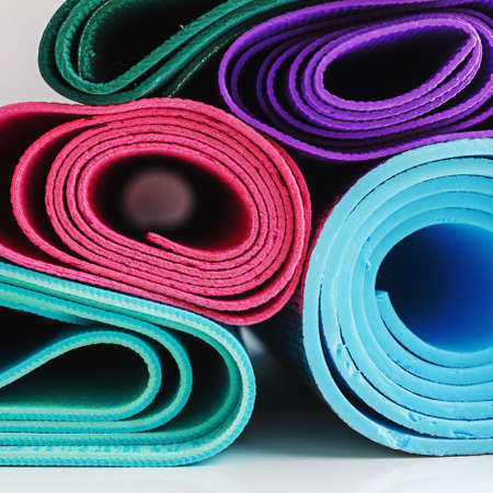 Stacked yoga mats of various bright colors, fitness themed background in a square frame