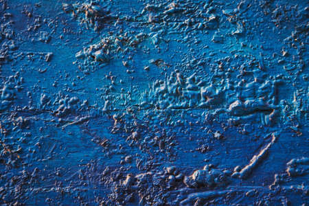 Bright turquoise blue painted textured surface made of construction foam on wood, creating various height and size elevations.