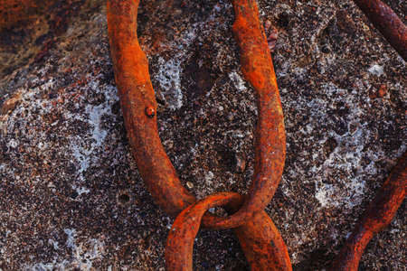 Links of rusty chain mounted into an old concrete construction