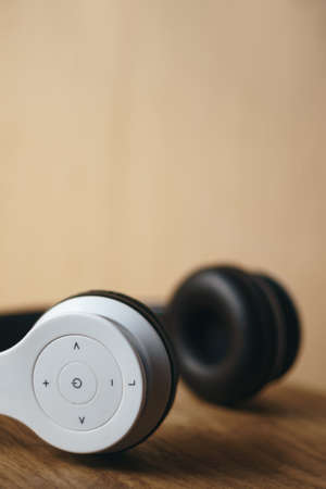 White wireless headphones placed on natural wooden surface on a blurred light wooden background in sunlight