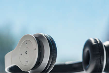 White wireless headphones placed on window ledge surface with blurred clear sky and trees on background in harsh sunlight