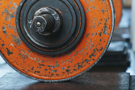 Old worn orange painted weight plates loaded onto a barbell standing on a black resin covered floor