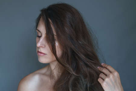 Retrato de una mujer joven tocando su mullido cabello castaño chocolate oscuro con la mano, mirando hacia abajo con expresión facial neutra. Foto de archivo