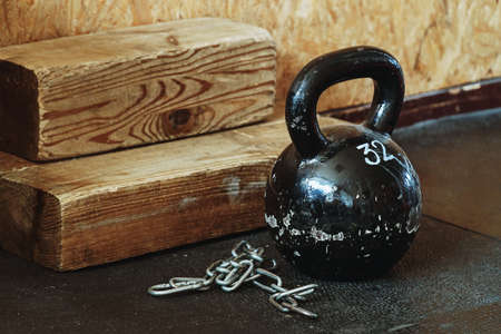 Old kettlebell covered in chapped glossy black paint standing on dusty floor in old gym