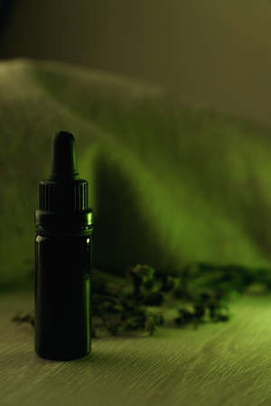 Single 10 ml black glass bottle surrounded with dried herbs on white wooden table backlit with green light