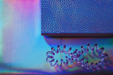 Abstract picture of set of holographic feminine objects - two various notebooks and cable hair band Stockfoto