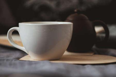 Witte porseleinen kopje thee en donkerbruine kleitheepot op een houten lasergesneden hart op grijs laken met boek en warme wollen sjaal op achtergrond
