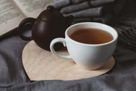 White porcelain cup of tea and dark brown clay teapot on a wooden laser-cut heart on grey bedsheet with book and warm woolen scarf on background