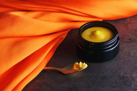 Beautiful picture of golden solid skincare oil in elegant black glass jar and golden spoon accentuated with bright orange silk cloth on dark grey stone Imagens