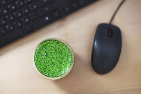 Top view of green smoothie on wooden work desk. Concept of healthy snacking during working day. Stockfoto