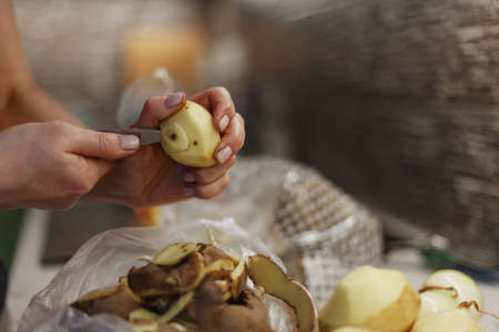 Woman's hands in process of peeling unwashed potato above small plastic bag