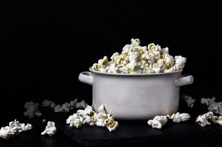 Popcorn in a white bowl on the black background. Copy space.