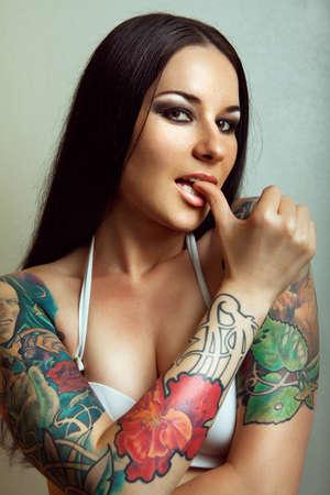 Beautiful girl with stylish make-up and tattooed arms  tattoo Stock Photo