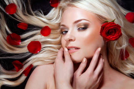 Beautiful girl with red roses in her blond hair  roses Stock Photo