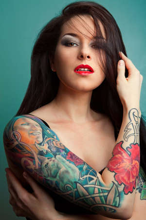 Beautiful sexy glamorous girl with tattoos.red. Stock Photo