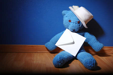Teddy bear with an envelope. blue background