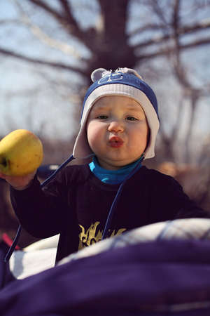portrait of a funny kid holding apple