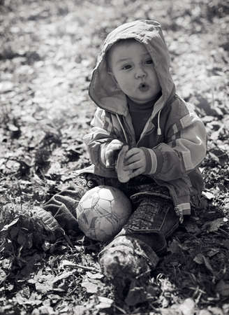 kid sits in an autumn park. boy. Stock Photo