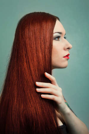 beautiful young woman with elegant long red shiny hair. hairstyle