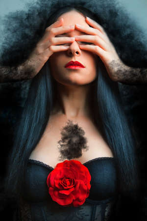 Vogue style photo of a gothic woman with red rose. photo