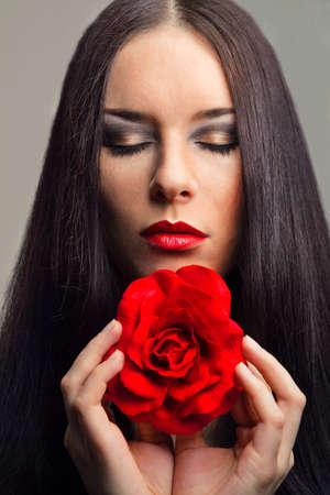 close-up portrait of beautiful brunette woman with red rose