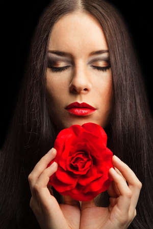 close-up portrait of beautiful brunette woman with red rose. dark background