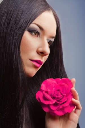 close-up portrait of beautiful brunette woman with pink rose