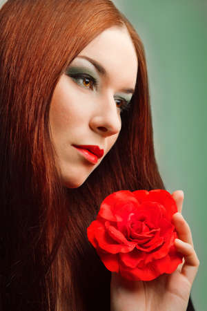close-up portrait of beautiful woman with red rose