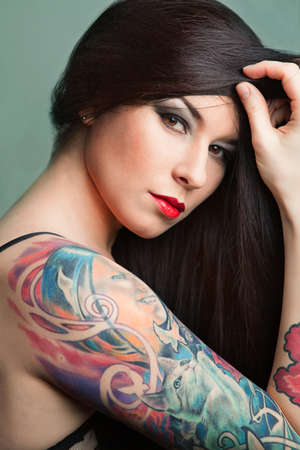 Beautiful girl with stylish make-up and tattooed arm