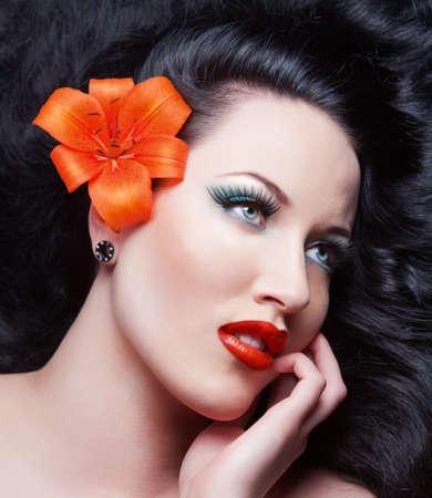 Beautiful Brunette Girl with flower. Healthy Long Hair.brunett Stock Photo
