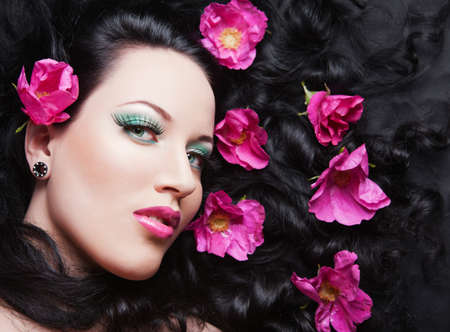 Young beautiful brunette girl with pink flowers in her hair. pink flower