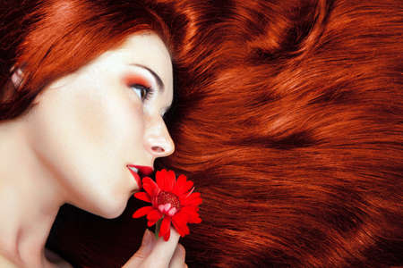 beautiful girl with gorgeous red hair. flower