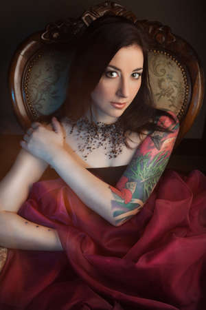 Beautiful girl with stylish make-up and tattooed arm. tattoo