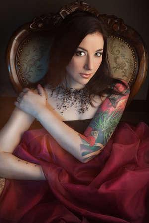 Beautiful girl with stylish make-up and tattooed arm. tattoo