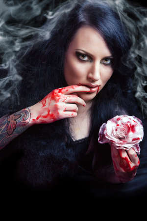 beauty vampire girl with blood on face on black background Stock Photo