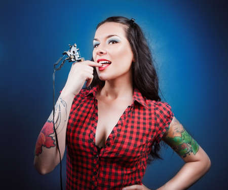 red bandana: Photo of beautiful girl with tattoos and tattoo machine tattoos