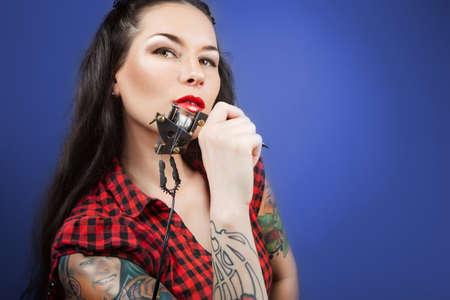 Photo of beautiful girl with tattoos and tattoo machine  tattoo machine photo