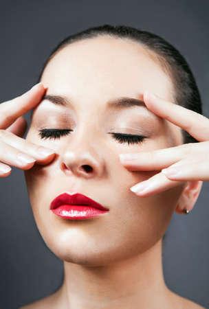 portrait of attractive caucasian woman making face massage  massage photo