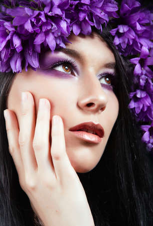 Close-up portrait of young beautiful  woman with flowers around her face photo