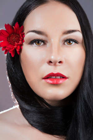 Portrait of young fresh beautiful healthy woman  red flower photo