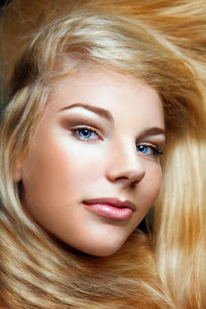 Close-up shot of young beautiful girl with long blond hair and stylish make-up