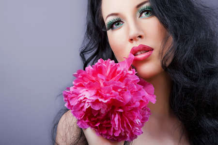Young beautiful brunette  girl with pink flower in her hair. pink flower