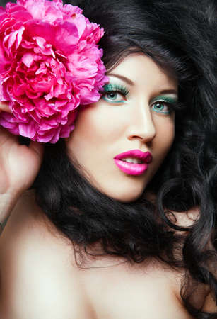 Young beautiful brunette  girl with pink flower in her hair. pink flower photo