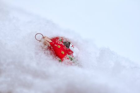 The red Christmas tree ornaments lies in the fluffy snow. 스톡 콘텐츠