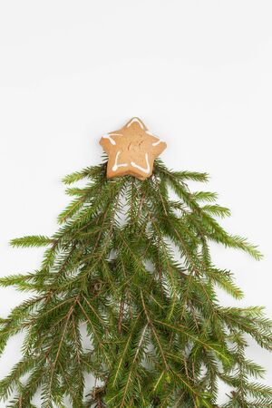 Mini Christmas tree made of fir branch decorated with cookie star on white background. New Year, holiday concept. Flat lay, top view